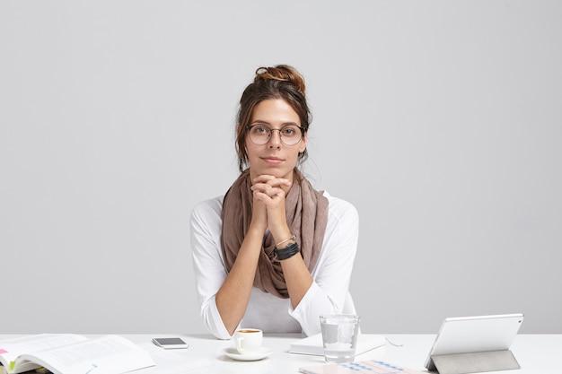 자신감이 넘치는 여성 기업가의 실내 샷은 사무실 책상에 앉아 새로운 프로젝트를 개발하고 있으며 커피 브레이크가 있습니다.