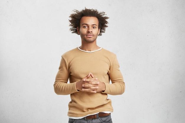 Снимок уверенного в себе бизнесмена смешанной расы, одетого небрежно, в помещении