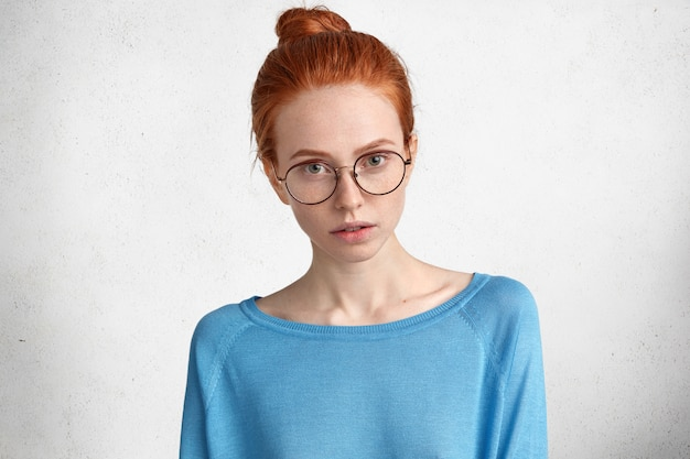 Снимок в помещении уверенной в себе серьезной студентки в очках, у нее рыжий пучок волос, она внимательно слушает, какую информацию ей следует подготовить, изолированная на белом