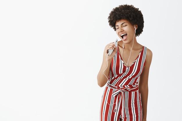 Кадр из помещения: креативная и счастливая беззаботная афроамериканка с афро-прической, держащая смартфон как микрофон, поет под музыку и радостно слушает песни в наушниках