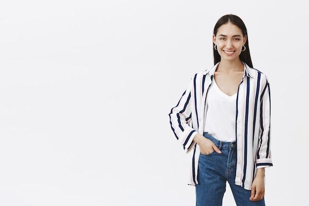 Снимок креативного симпатичного стильного дизайнера в полосатой блузке и стильных джинсах, держащего руку в кармане и широко улыбающегося, стоящего в расслабленной и уверенной позе над серой стеной в помещении