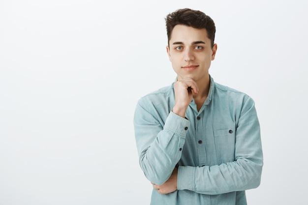 Снимок любопытного красивого кавказского мужчины в повседневной одежде в помещении