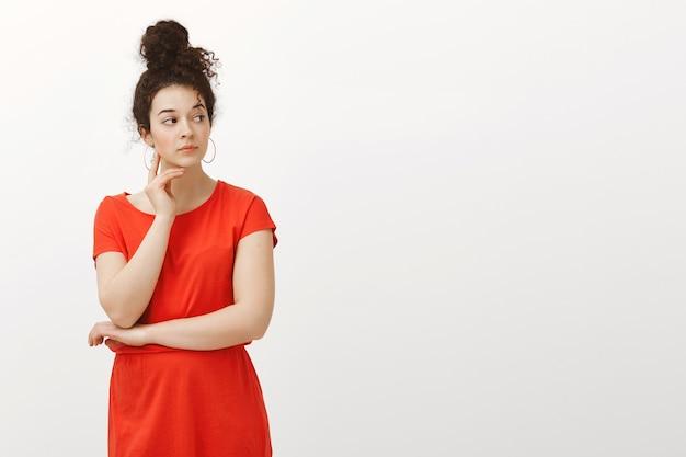 빨간 드레스를 입고 롤빵에 빗질 곱슬 머리를 가진 호기심 심각한 여성의 실내 촬영