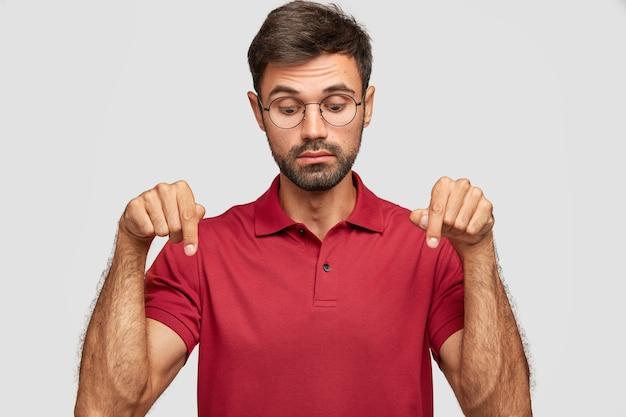 興味をそそる表情で好奇心旺盛な無精ひげを生やした若い男の屋内ショット、両方の人差し指で下向き