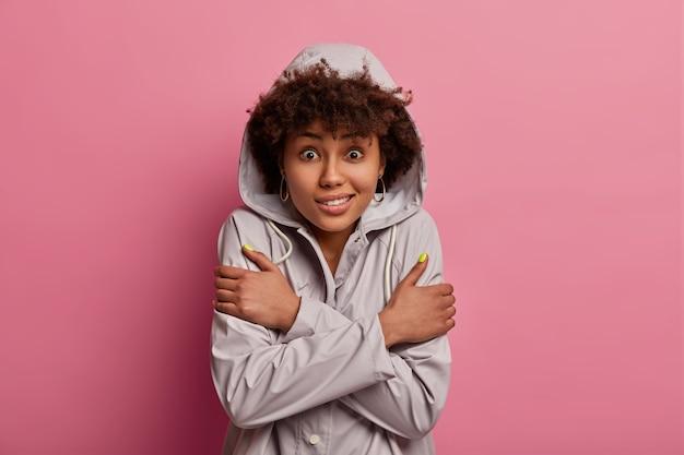 巻き毛の女性の屋内ショットは、凍えそうに感じ、体に腕を組んで、寒さから震え、フード付きのレインコートを着て、凍るような天候の間に歩き、バラ色の壁に隔離され、ウォームアップする必要があります。