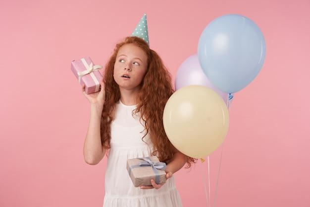 Снимок в помещении: милая девочка с рыжими кудрявыми волосами в белом платье позирует на розовом фоне, празднует день рождения и получает подарки, держит подарочные коробки и задается вопросом, что же внутри