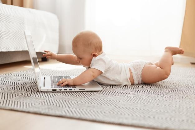 おなかの床に横たわって、灰色のカーペットの上で、ラップトップコンピューターに触れて、明るい部屋で一人でポーズをとっている白いtシャツを着ているかわいい好奇心旺盛な女の赤ちゃんまたは男の子の屋内ショット。