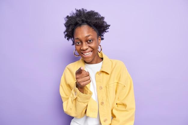 Снимок симпатичной темнокожей женщины с вьющимися волосами в помещении указывает прямо на камеру