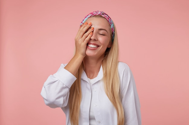 彼女の顔に手のひらと目を閉じて、色付きのヘッドバンドと白いシャツを着て、立って、心地よく不思議に見えるかわいい女の子の屋内ショット