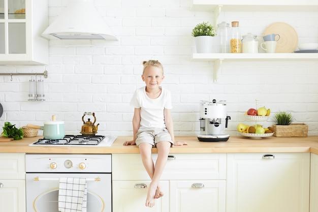 금발 머리 롤빵이 세련된 부엌에서 카운터에 앉아 귀여운 잘 생긴 어린 소년의 실내 샷, 그의 맨발에 매달려, 어머니가 학교 전에 아침에 아침 식사를 요리하기를 기다리고 있습니다.