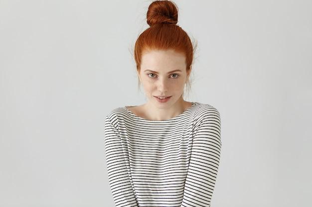 Снимок милой рыжей европейской девушки с веснушками и пучком волос в помещении, застенчиво улыбаясь