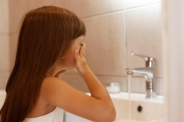Крытый снимок темноволосой девочки, стоящей в ванной и умывающей лицо после пробуждения или перед сном, гигиенические процедуры в домашних условиях.