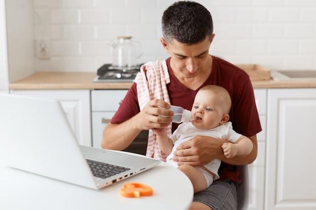 肩にタオルでカジュアルなtシャツを着て、ラップトップでテーブルに座って、女の赤ちゃんを手に持って、ボトルから彼の娘に水を与える黒髪のハンサムな男の屋内ショット。