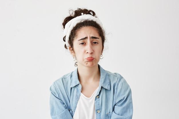 暗い髪の動揺している女性が誰かに虐待されている屋内のショット、唇のカーブ、眉をひそめている、不幸に見える、白い壁に分離されたデニムのシャツを着ています。否定的な人間の感情と感情