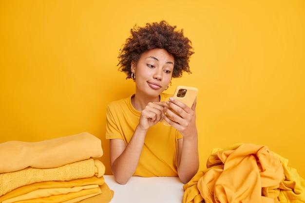 Снимок темнокожей кудрявой женщины в помещении проверяет ленту новостей через смартфон