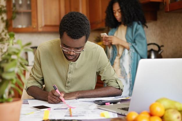 ピンクのフェルトペンを使用して台所のテーブルに座っている浅黒い肌の男の屋内撮影