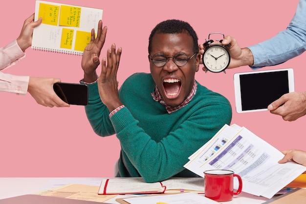 絶望的な若いアフロアメリカ人男性の屋内ショットは必死に叫び、停止ジェスチャーを行い、緑のセーターを着て、忙しく働いて、ピンクの背景の上に孤立しています。人