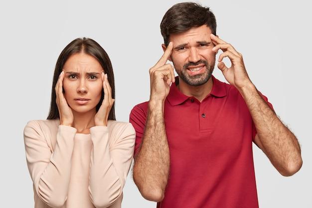 絶望的な女性と男性の同僚の屋内ショットは、こめかみに指を置き、不満に見えます