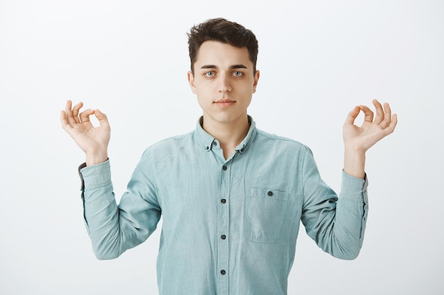 Снимок целенаправленного привлекательного мужчины в рубашке в помещении