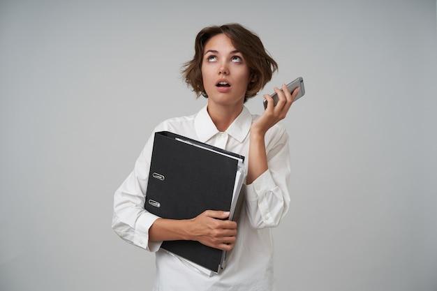 Снимок растерянной молодой брюнетки в строгой одежде в помещении, позирует со смартфоном и папкой с документами, скучно разговаривает и закатывает глаза