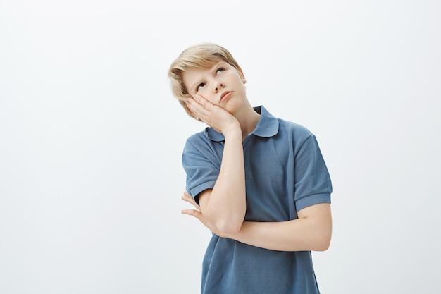 Снимок в помещении: недовольный скучающий симпатичный белокурый мальчик, склонивший голову на ладонь и смотрящий вверх, хмурый и мрачный, будучи наказанным за непослушание.