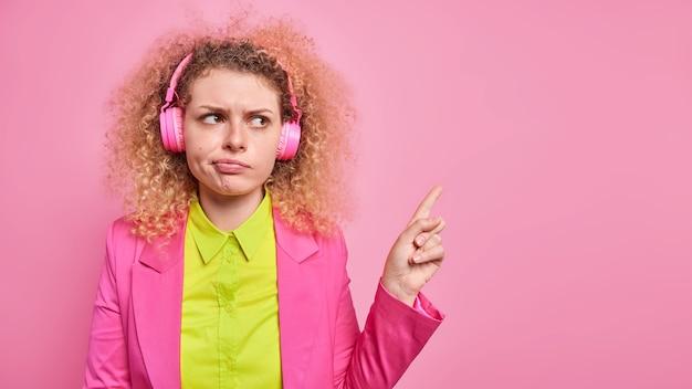 不機嫌な巻き毛の若い女性の屋内ショットは、右上隅に何か不快な様子を示し、正式な服装をし、ピンクの壁に隔離されたヘッドフォンで音楽を聴いている