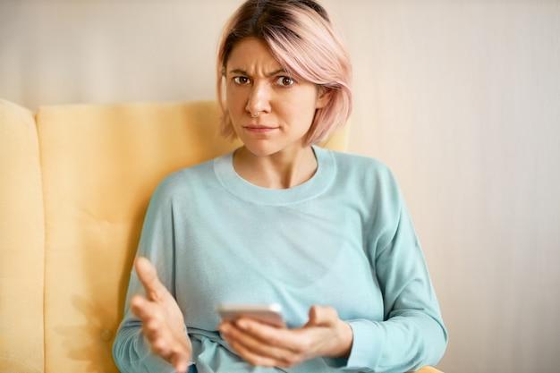 携帯電話のソファに座って、接続の問題やバッテリーの充電量が少ない、イライラした表情でカメラを見ている青いスウェットシャツの不快なイライラした若い女性の屋内ショット