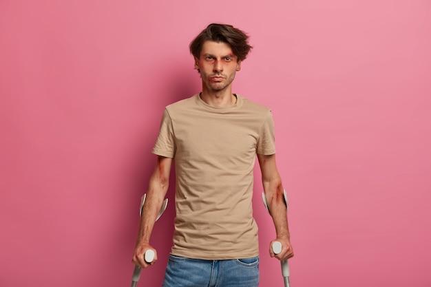 傷のある不機嫌な男性の屋内ショットは、深刻な病気の後に回復し、リハビリ期間があり、ひどい自動車事故に巻き込まれ、松葉杖でポーズをとるには、医師の診察を受ける必要があります