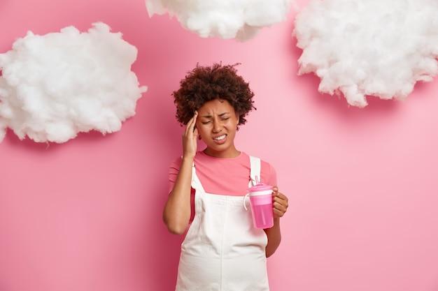 不機嫌な妊婦の屋内ショットは、頭痛に苦しみ、耐え難い片頭痛を感じ、大きなおなかを持ち、水を飲み、カジュアルな服を着て、ピンクの壁に隔離されています。家族と妊娠