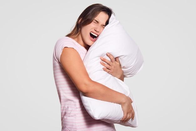 Снимок в помещении недовольной женщины широко раскрывает рот, имеет недовольное выражение лица, держит в руках белую подушку, носит повседневную домашнюю одежду, модели в помещении, расстроенные из-за ужасных снов ночью