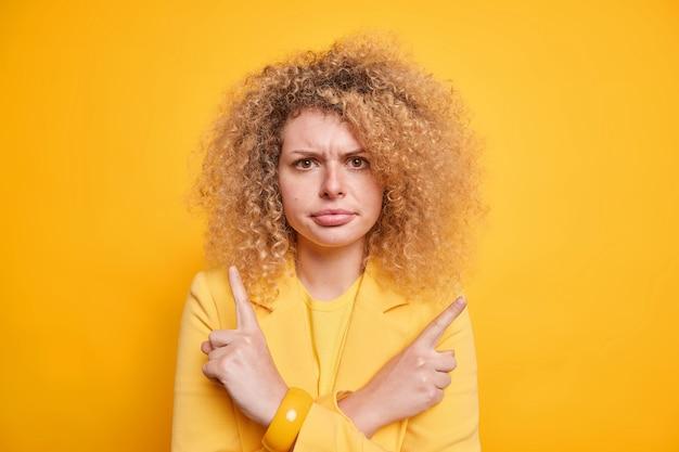 不満のある巻き毛の若い女性の屋内ショットは、横向きに顔のポイントを笑い、2つのオプションから選択することを躊躇していると感じています
