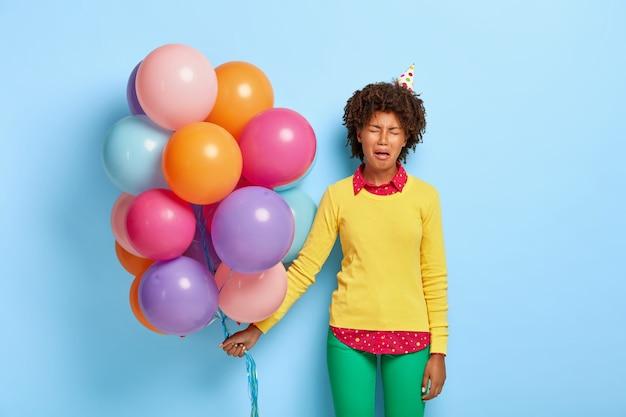 Снимок неудовлетворенной темнокожей женщины, сделанный в помещении, чувствует себя прекрасно и расстроен во время особого праздника