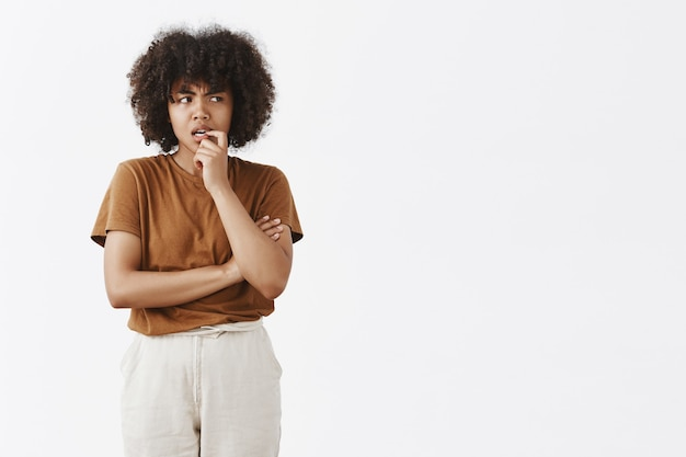 Снимок в помещении сомнительной и сомнительной молодой афро-американской женщины с афро-прической в коричневой футболке, кусающей ноготь и хмурящейся, смотрящей прямо во время принятия решения или размышлений