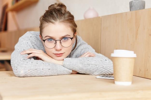 Крытый снимок очаровательной мечтательной женщины в круглых очках