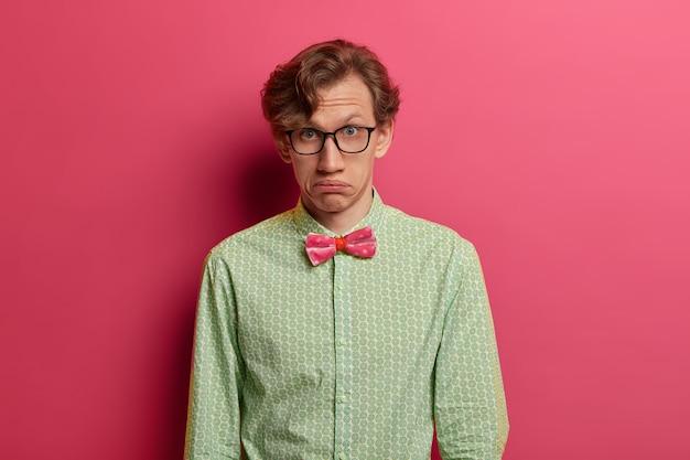 Снимок в помещении: смущенный удивленный мужчина выглядит сомнительно, поджимает губы, носит очки, строгую рубашку и розовую бабочку, смотрит прямо, изолированно на розовой стене. выражения человеческого лица