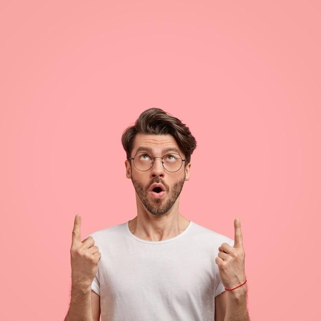 Внутренний снимок эмоционального небритого мужчины с модной прической, темной щетиной, от удивления открывает рот, показывает обоими указательными пальцами, показывает свободное место для вашего рекламного контента, одетый небрежно