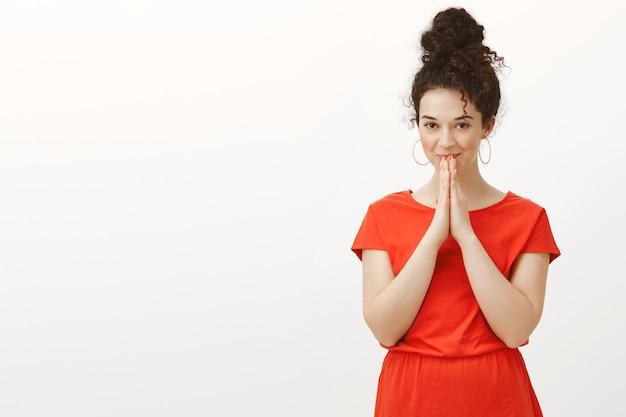 赤いドレスを着た邪悪な見栄えの良い女性の屋内ショット