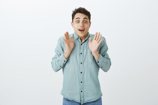 Крытый снимок взволнованной счастливой мужской модели в повседневной рубашке