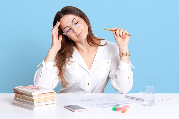 Крытый выстрел измученной молодой темноволосой бизнесвумен, сидя в офисе на белом столе, держит глаза закрытыми, касаясь ее лба, выглядит усталым от работы с бумагами. люди и концепция работы.