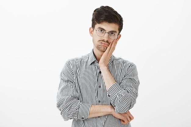 ストライプのシャツを着たうんざりした退屈な成熟した男性モデルの屋内ショット。頬に手のひらを押し、息を切らして、無関心と退屈を凝視し、長いオフィスミーティングに悩まされています。