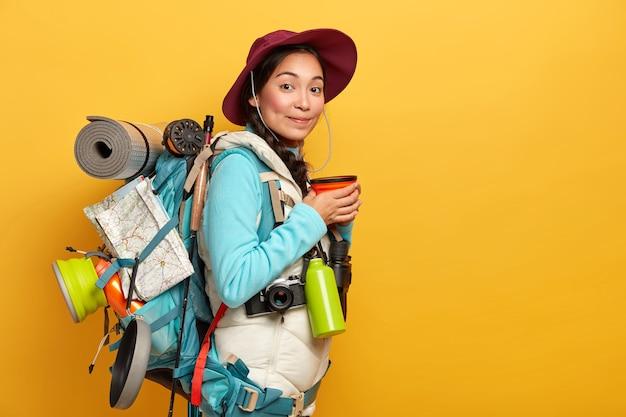 여성 여행자의 실내 촬영은 커피를 마시고, 여행을 즐기고, 필요한 물건과지도가 들어있는 배낭을 들고, 긴 경로를 가지고 있으며, 모자와 편안한 옷을 입고 있습니다.