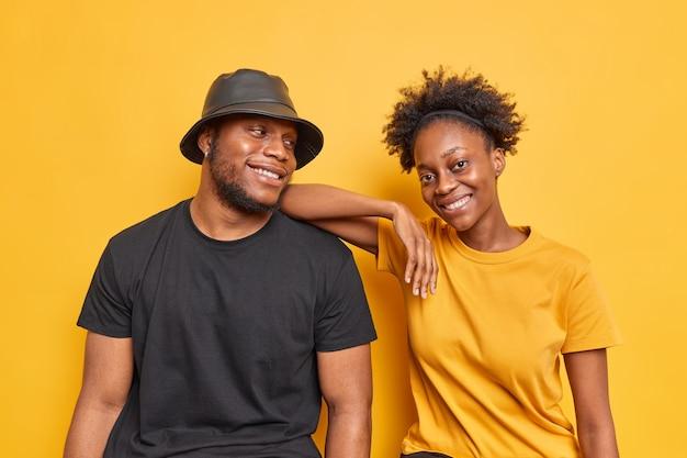 フレンドリーな暗い肌のボーイフレンドとガールフレンドの屋内ショットは、カジュアルな服を着て一緒に自由な時間を過ごします鮮やかな黄色で幸せに分離された笑顔