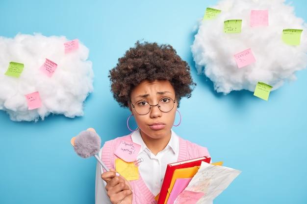 Снимок в помещении: разочарованная несчастная афроамериканка, собирающаяся выполнять домашнее задание, держит папки с бумагами и ручку носит круглые очки в аккуратной одежде делает пометки на наклеенных вокруг стикерах