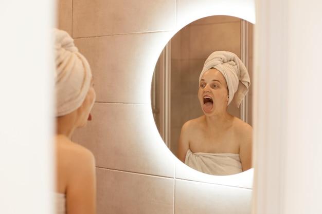 Крытый снимок смешной женщины, стоящей в ванной с белым полотенцем на голове, смотрящей на свое отражение в зеркале с широко открытым ртом, показывая язык.
