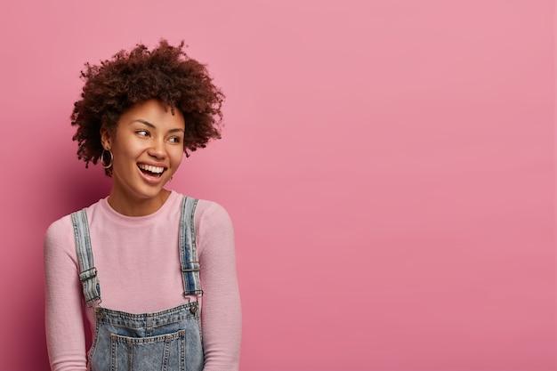 Снимок довольной афроамериканки в помещении, отводит взгляд, позитивно смеется, замечает что-то приятное, носит полонек и джинсовый сарафан, весело наслаждается моментом, изолировано на розовой пастельной стене