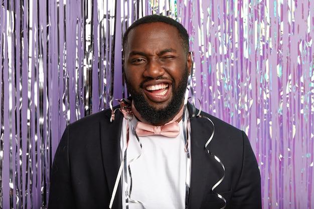Снимок в помещении: довольный темнокожий мужчина что-то празднует, моргает, у него зубастая улыбка, в элегантном костюме и розовом галстуке-бабочке, он позирует над фиолетовой стеной с мишурой, находится на дискотеке концепция праздничного мероприятия