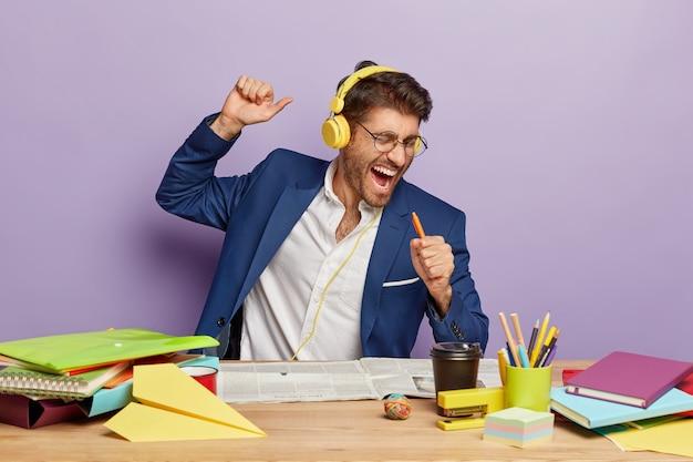 Крытый снимок радостного смешного бизнесмена, сидящего за офисным столом