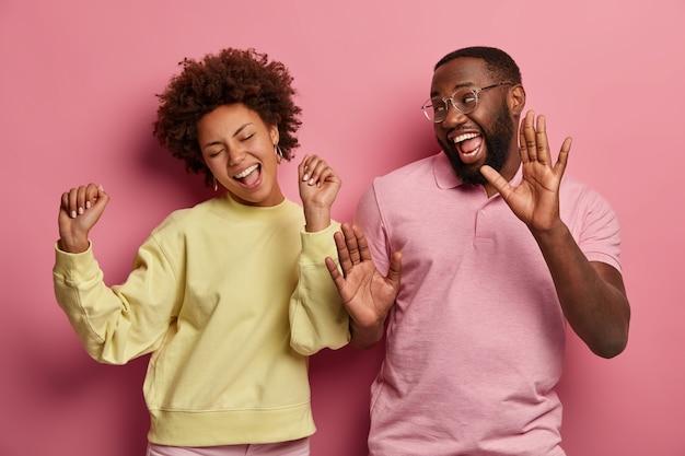 기쁜 여자 친구와 남자 친구의 실내 샷은 기쁨으로 힙합을 춤추고, 무언가를 축하하고, 웃고 손으로 움직이고, 안경, 점퍼 및 티셔츠를 입습니다.
