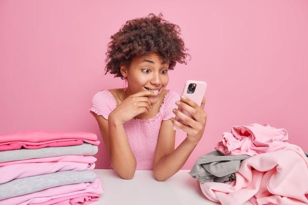 アフロの髪の嬉しい女性の屋内ショットは、家事をした後、休憩を取り、服を折りたたむと、スマートフォンのニュースフィードがピンク色で隔離されたテーブルに座っていることを確認します