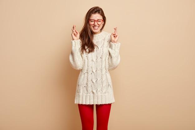 Снимок в помещении: довольная женщина с довольным выражением лица, держит пальцы скрещенными, надеется, что мечты сбываются, в длинном свитере и колготках, изолирована от бежевой стены. верьте только в лучшее!